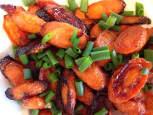 A close up of roasted carrots topped with sliced green onions.