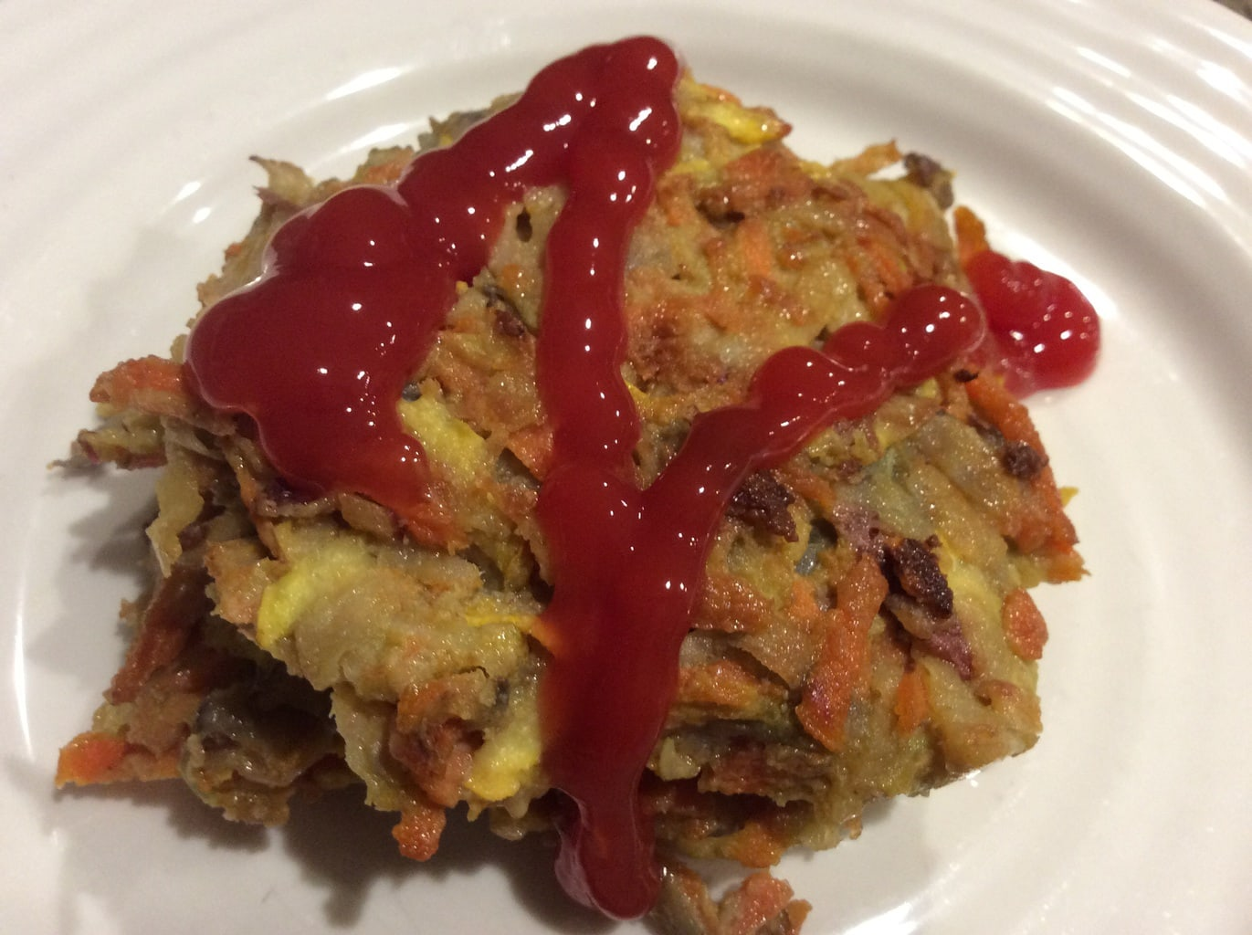 Veggie pancakes on a white plate and drizzled with ketchup.