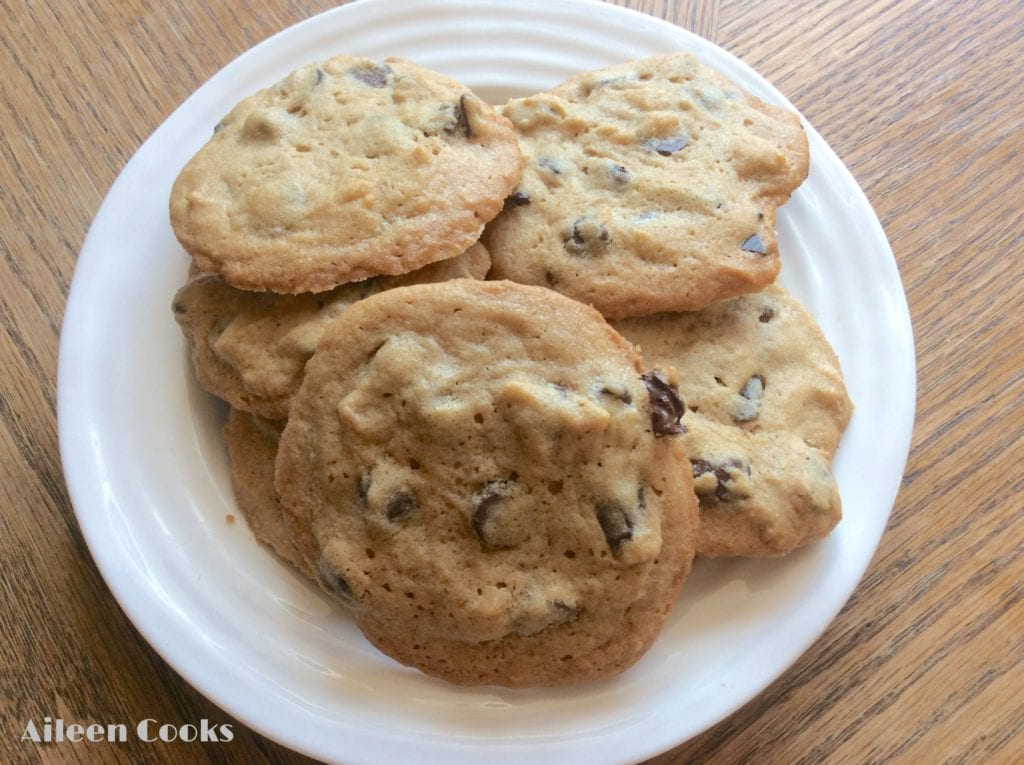 A white plate piled with soft peanut butter chocolate chunk cookies.