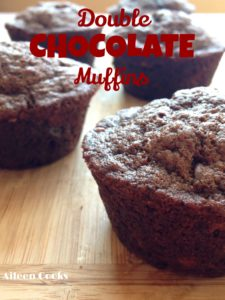 A line of double chocolate muffins on a wooden table.