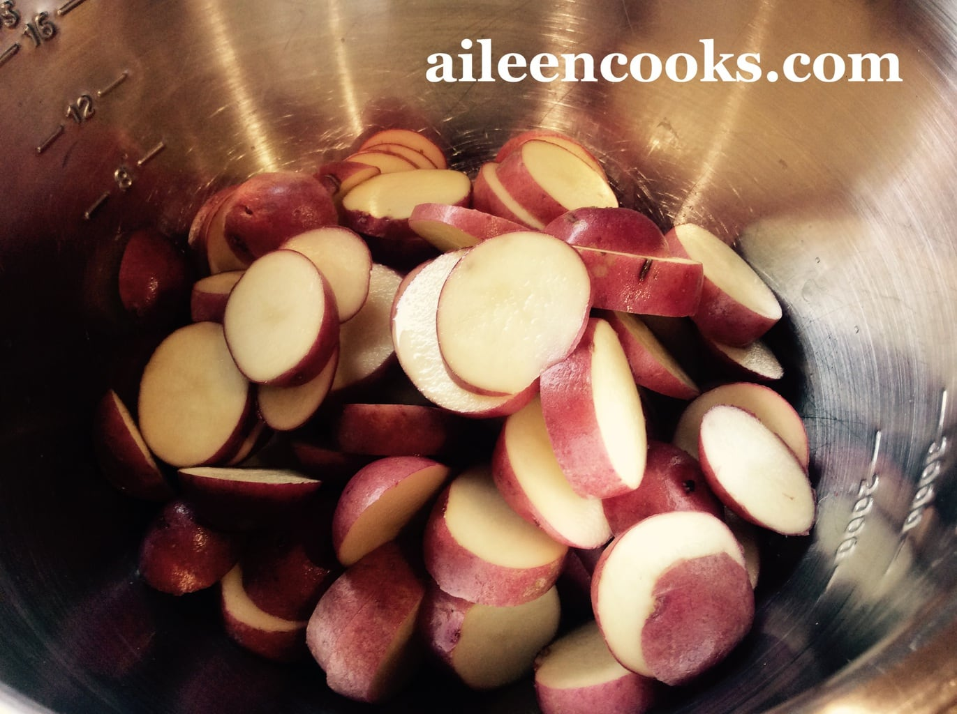 A metal mixing bowl filled with small red potatoes sliced 1/2 inch thick.