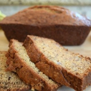 Three slices of banana bread in front of a loaf of banana bread.