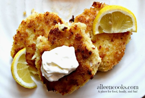 Three tilapia cakes topped with sour cream and lemon wedges.