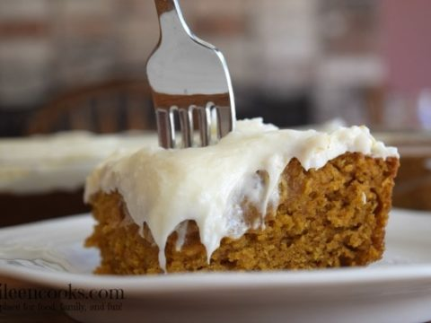 A slice of pumpkin sheet cake with cream cheese frosting with the fork sticking out of the top of the cake.