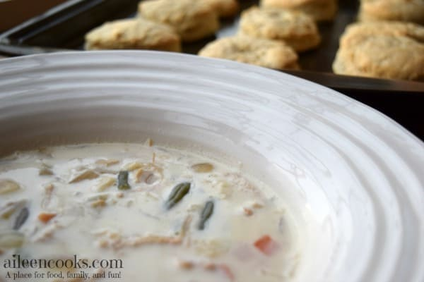 Close up of slow cooker chicken pot pie soup with cookie sheet of fresh baked biscuits in the background.