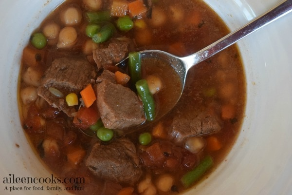 A bowl full of pressure cooker vegetable beef soup filled with green beans, chunks of beef, carrots, garbanzo beans, and corn.
