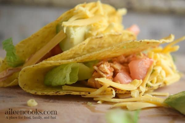 instant pot salsa chicken tacos - an instant pot frozen chicken recipe -in crispy taco shells with fresh tomato and lettuce