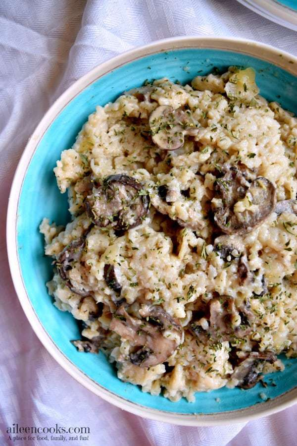 Blue bowl with instant pot mushrooom risotto inside on a white tablecloth