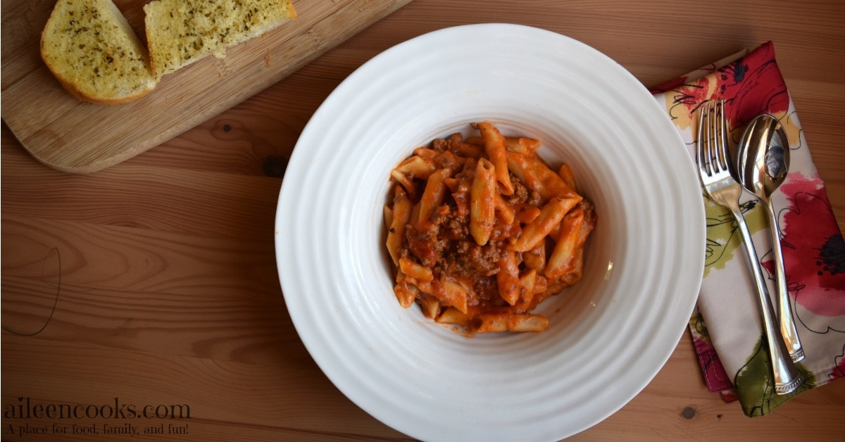 Pressure cooker baked ziti served in a large rimmed white bowl.