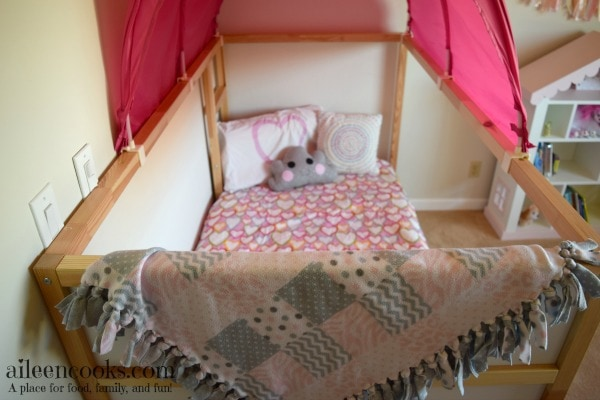 Little girl's bed with a pink tent canopy on top.