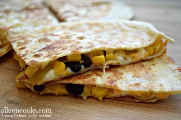 Corn and black bean quesadillas cut into triangles and stacked on a wooden cutting board.