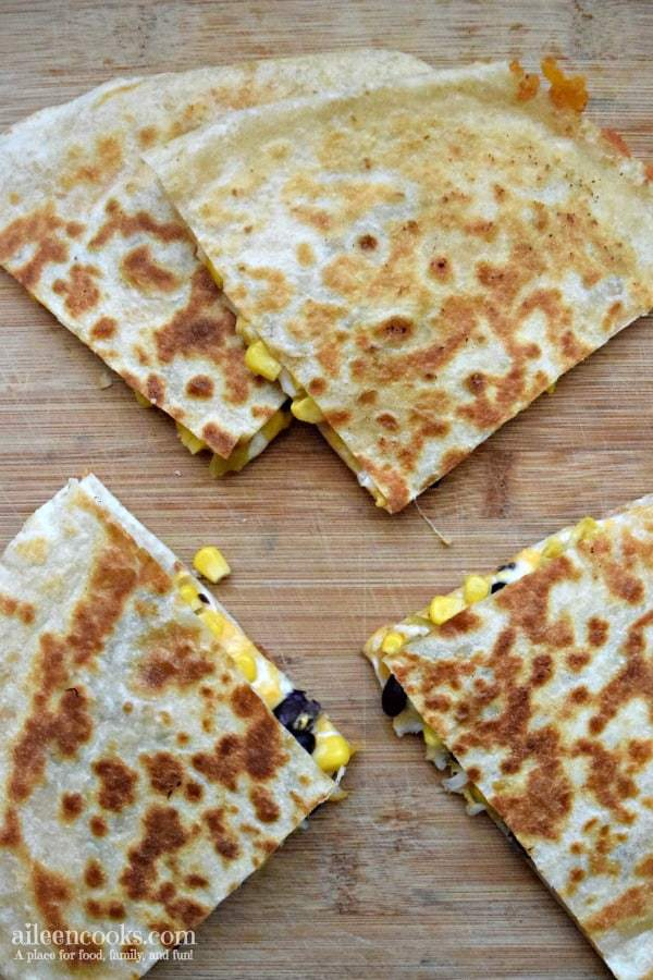 Black bean and corn quesadillas on a wooden cutting board with a few pieces of corn falling out.