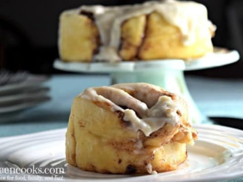 Cinnamon roll on a white plate with additional cinnamon rolls on a cake stand in the background.
