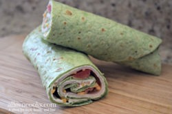 Spinach wrap rolled up with turkey, cheese, and tomatoes peeking out.