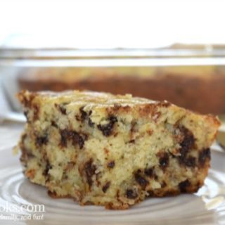 close up of slice of banana chocolate chip cake with whole cake in the background