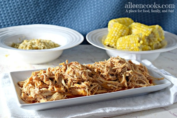 White serving dish with shredded buffalo chicken with bowl of corn in the background.