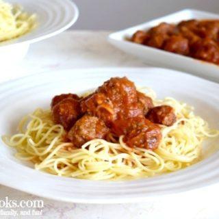 bowl of spaghetti, platter of italian meatballs, and plate with spaghetti, meatballs, and marinara.