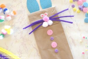 easter bunny hand puppet made with paper lunch bag, buttons, pipe cleanrs, and cotton balls.