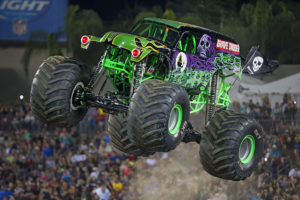 Green monster truck driving over dirt and catching air.