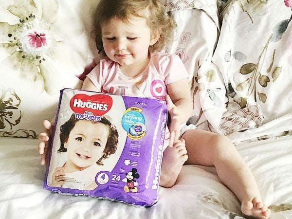 Brown haired toddler on bed holding bag of diapers.