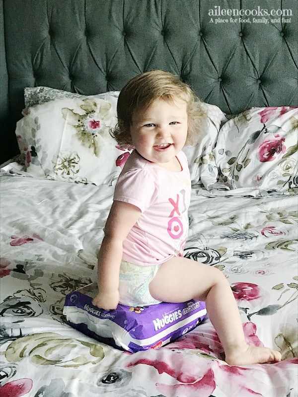 smiling baby sitting on package of diapers