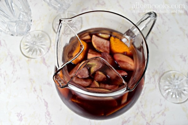 pitcher of red wine sangria with chopped apples and oranges.
