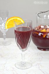 glass of red wine sangria with orange slice.