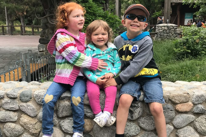 three kids sitting on rock wall at disneyaland california adventure.