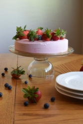 no-bake strawberry cheesecake on glass cake stand