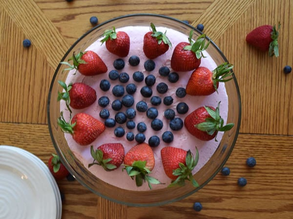 no-bake strawberry cheesecake on glass cake plate and topped with fresh berries.