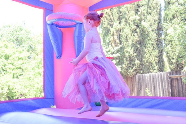 ballerina party birthday girl jumping in castle bounce house in glitter tutu.