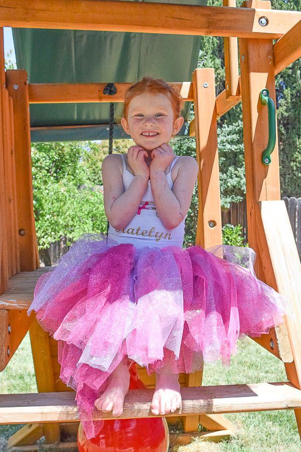 birthday girl in pink and purple tulle tutu and custom shirt with ballerina, her name, and age.