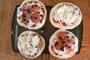 4 homemade freezer pizzas. 2 are plain cheese and 2 are pepperoni and olive, all sitting on top of a large cookie sheet.
