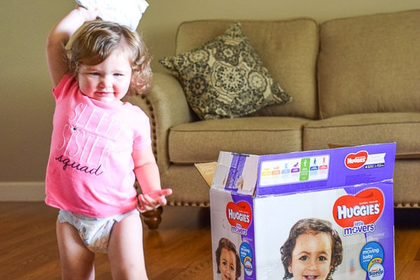 Toddler girl in pink shirt and diaper smiling and standing next to open box of diapers.