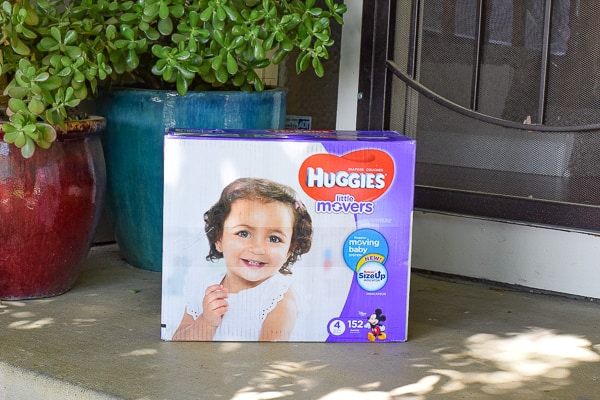 Box of huggies diapers sitting on a front porch.