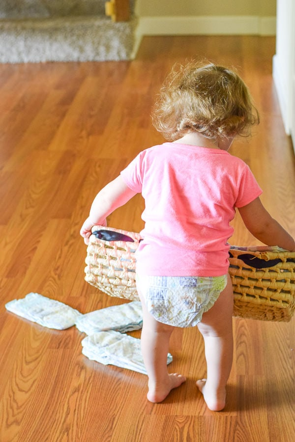 toddler in a diaper and pink shirt carrying a basket of diapers and dropping them on the floor