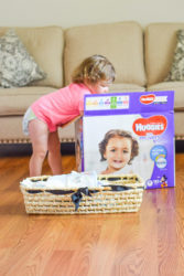 Toddlerin a pink shirt taking diapers out of a box.
