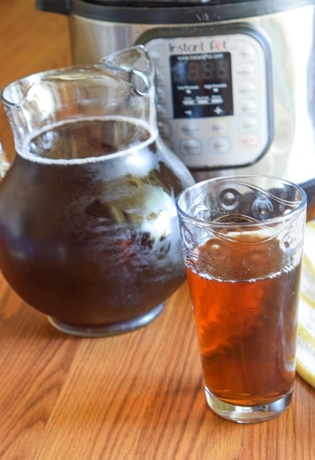 Pitcher of iced tea and glass of iced tea set in front of instant pot electric pressure cooker on a wood surface.