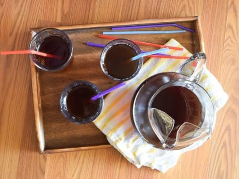 Overhead shot of wood tray holding piture of instant pot iced tea, 3 glasses of iced tea, colorful straws, and yellow striped towel.
