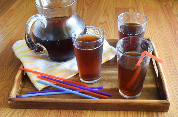 Serving tray with pitcher of iced tea, 3 glasses filled with iced tea, a stack of colorful straws and yellow and white striped towel.