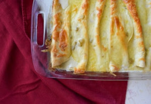 sour cream chicken enchiladas in baking dish over red cloth napkin.