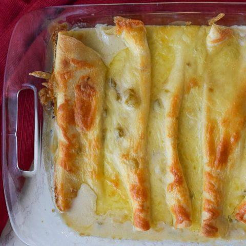 chicken enchiladas in a white sauce sitting in a baking dish.