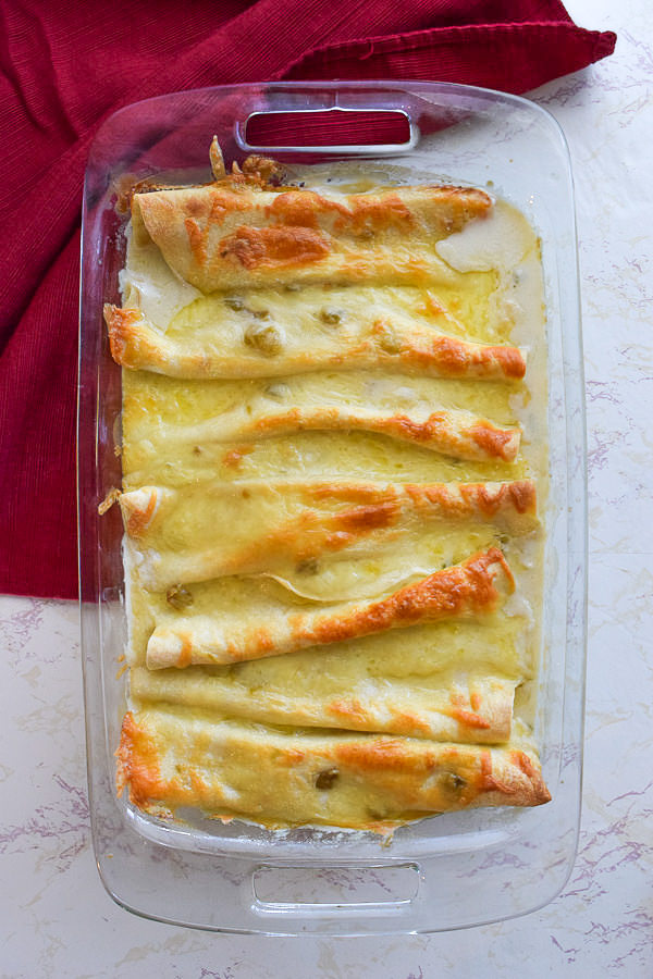 Glass baking dish with chicken enchiladas in sour cream white sauce.