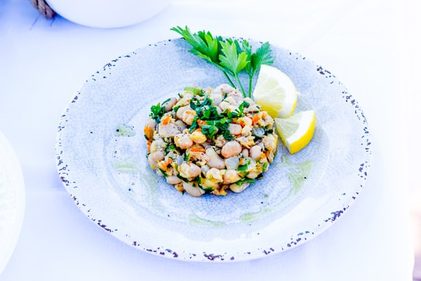 white bean tuna salad on a white and blue plate with sprig of parsley and lemon slices.