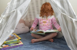 Inside a reading nook filled with soft pillows, books, and a little girl reading to herself.