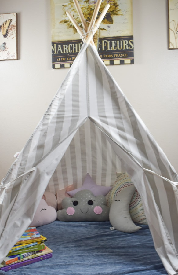 Cozy reading nook made up of a grey and white striped teepee, blue fleece blanket, and several throw pillows in grey, light pink, and white.