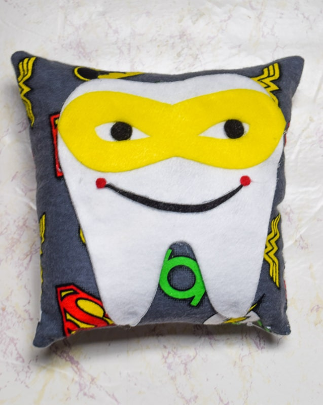 Superhero tooth fairy pillow made with the cricut maker using cotton superhero printed fabric and various colors of felt.