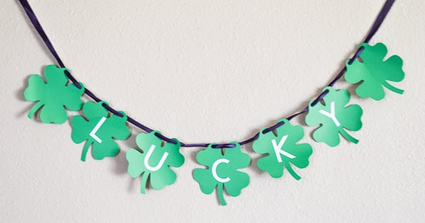 "St. Patrick's Day Banner of green clovers with white letters on top spelling out ""lucky"" made with the cricut maker."