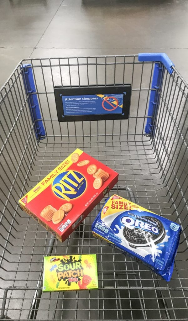 Walmart shopping cart filled with ritz crackers, oreo, and sour patch kids.