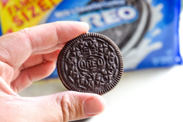 Close up of a hand holding an oreo cookie in front of a box of oreo cookies.